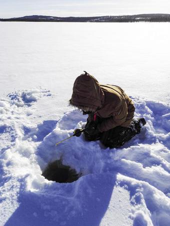 Angler vor dem Eisloch